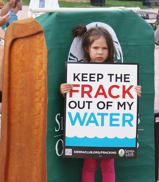 Young girl standing in front of wooden podium, holding anti-fracking sign.