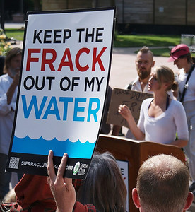 Young woman speaks from podium at anti-fracking rally, crowd of people listening, in foreground one protester holds sign in the air.