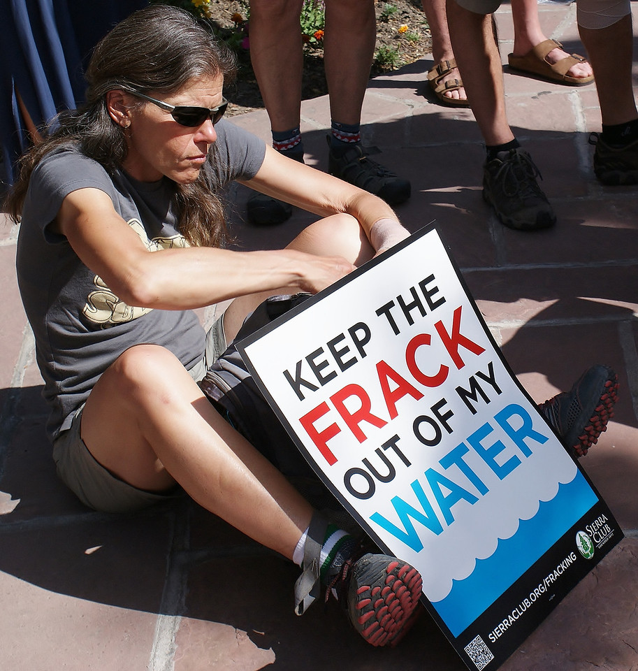 man with anti-fracking sign sits on pavement at rally.