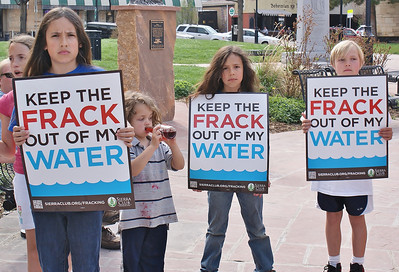 "Young children holding signs, ""Keep The Frack Out Of My Water"" at protest. One drinking from a bottle, something spilled on shirt."