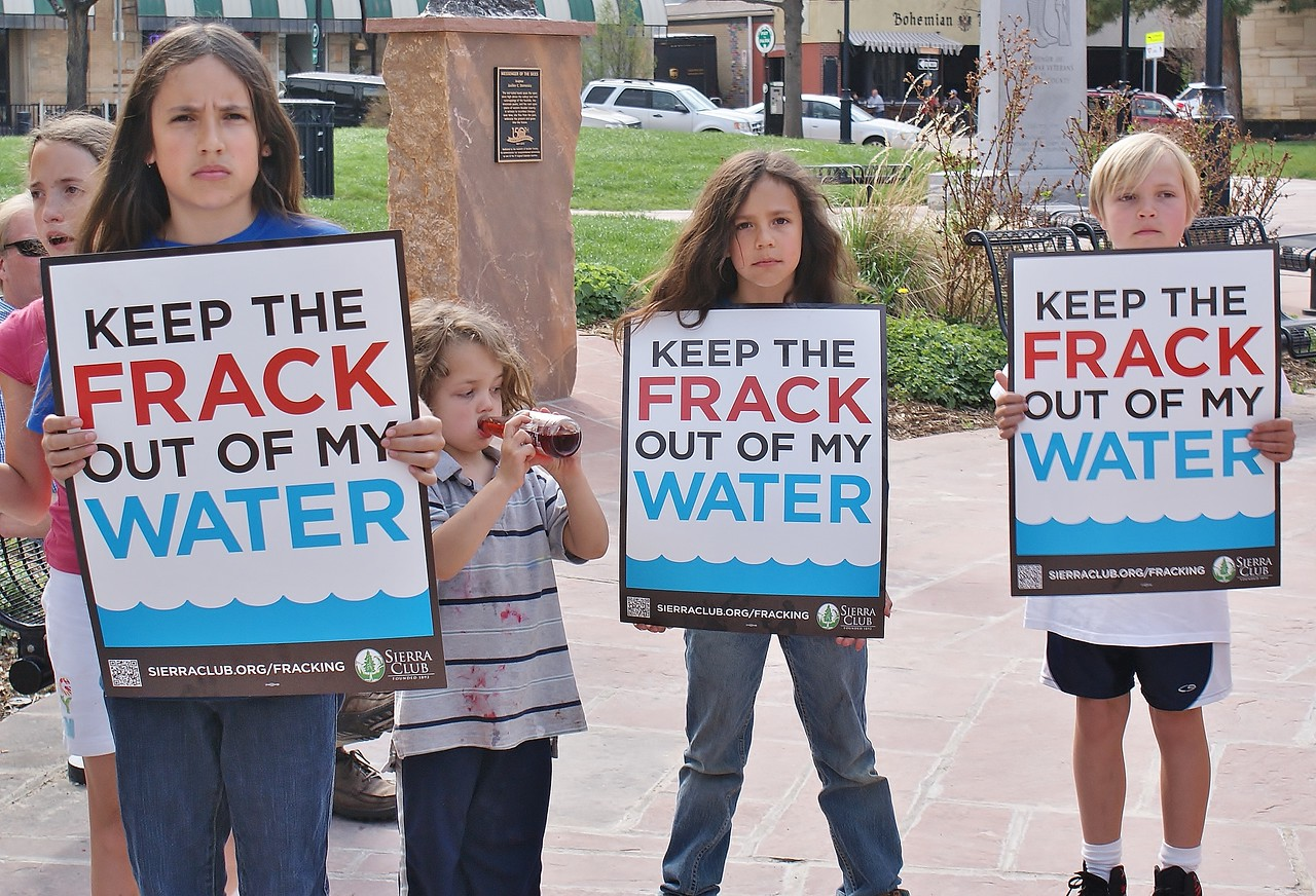 """Young children holding signs, """"Keep The Frack Out Of My Water"""" at protest. One drinking from a bottle, something spilled on shirt."""