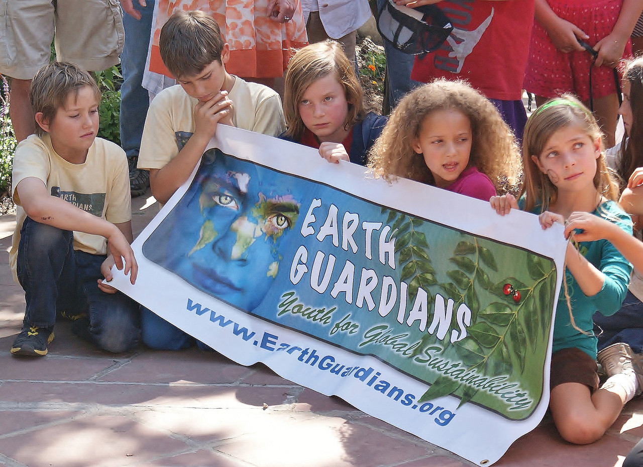 """Young children holding large """"Earth Guardians"""" banner, sitting and listening to speaker at rally."""