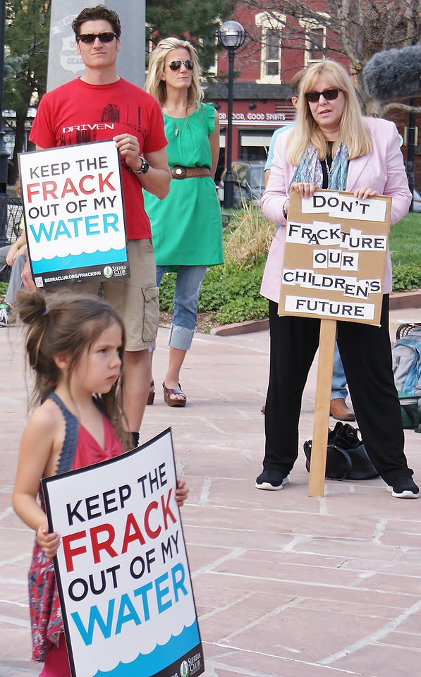 Young child holds anti fracking sign at protest, adults behind her with signs.