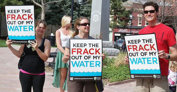 Three anti-fracking protesters hold sign about water safety at demonstration.
