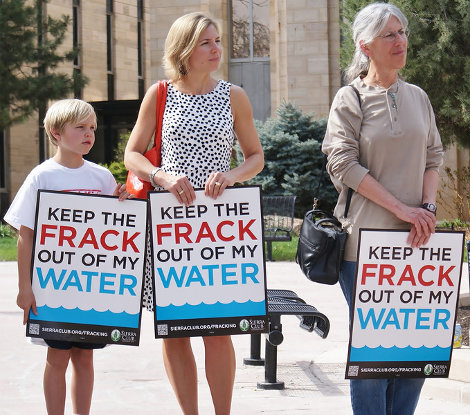 Two women and young boy holding anti-fracking signs at demonstration.