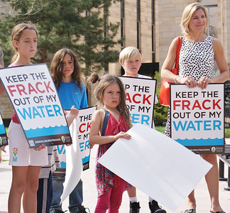 "Young children and woman holding ""Keep The Frack Out Of My Water"" signs at demonstration."