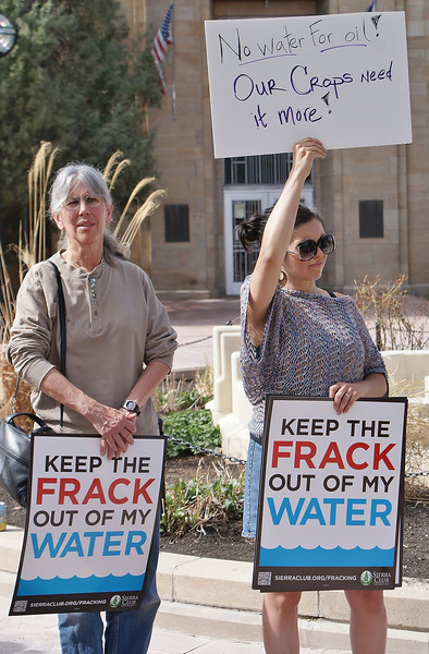 Two women holding sign about fracking and water at protest.