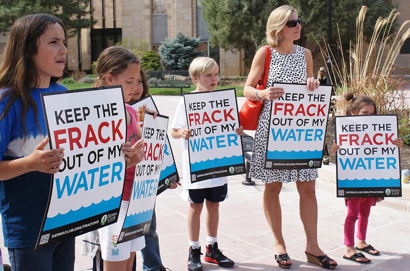 """Young children and woman holding """"Keep The Frack out Of My Water"""" signs at demonstration."""
