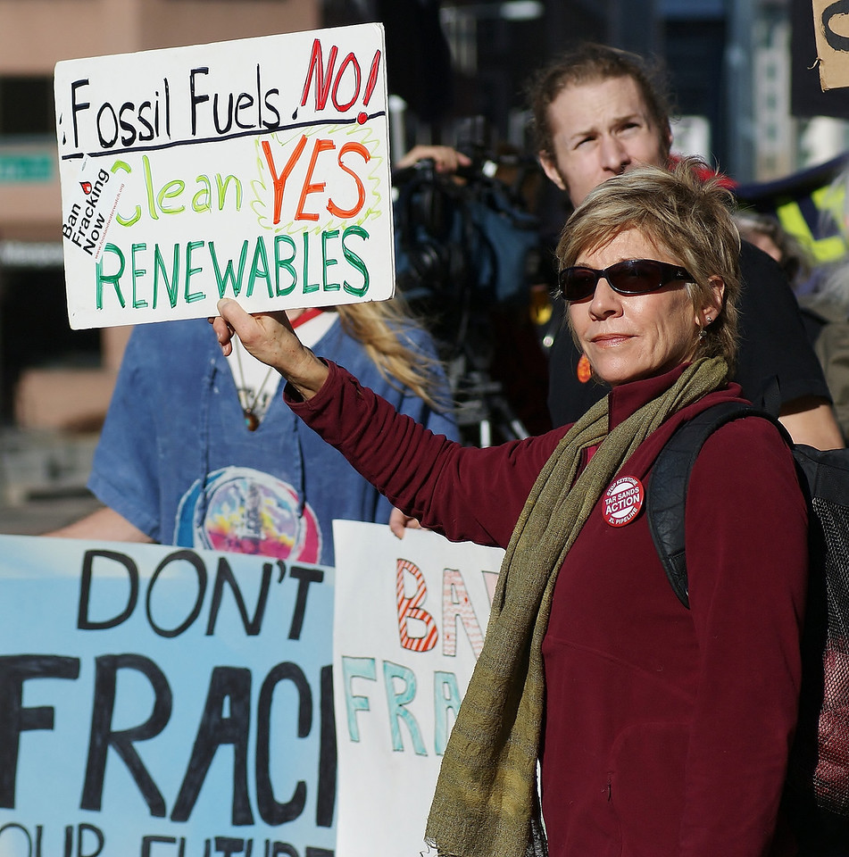 Woman holding sign about renewable energy, other anti-fracking protesters standing behind her.