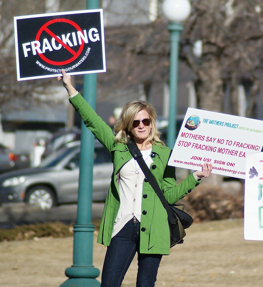 Woman holds anti-fracking sign above her head.
