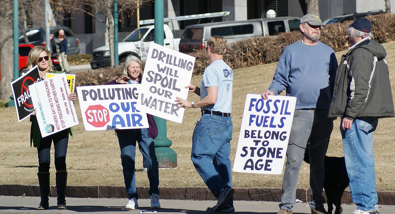 Protesters at anti-fracking demonstration with signs about fossil fuels, clean air and pollution of water.