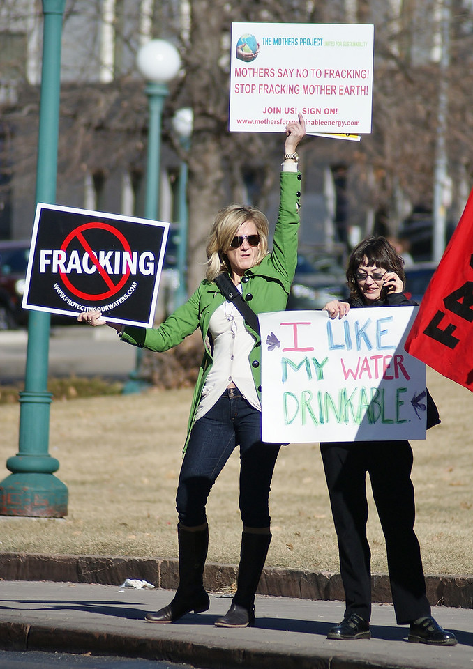 Woman holds anti-fracking sign above her head, next to her, another protester with sign talking on cellphone.