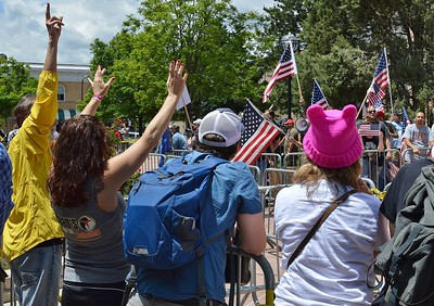 """Counter demonstrators at rally held by the alt right group """"The Proud Boys"""" raise their hands in the peace sign."""