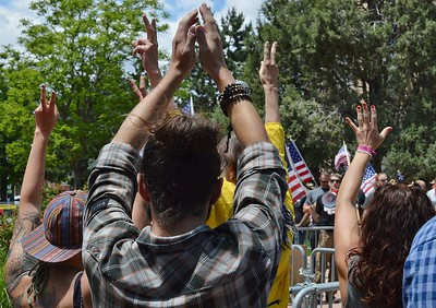 "Counter demonstrators at rally held by the alt right group ""The Proud Boys"" raise their hands in the peace sign."