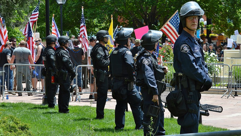 """Police in Boulder Colorado, some in riot gear, keep watch at a rally held by the alt-right group """"The Proud Boys"""", which drew about 300 counter protesters."""