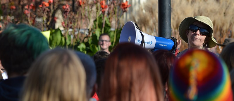 Woman speaking through bullhorn at rally protesting President-elect Donald Trump.