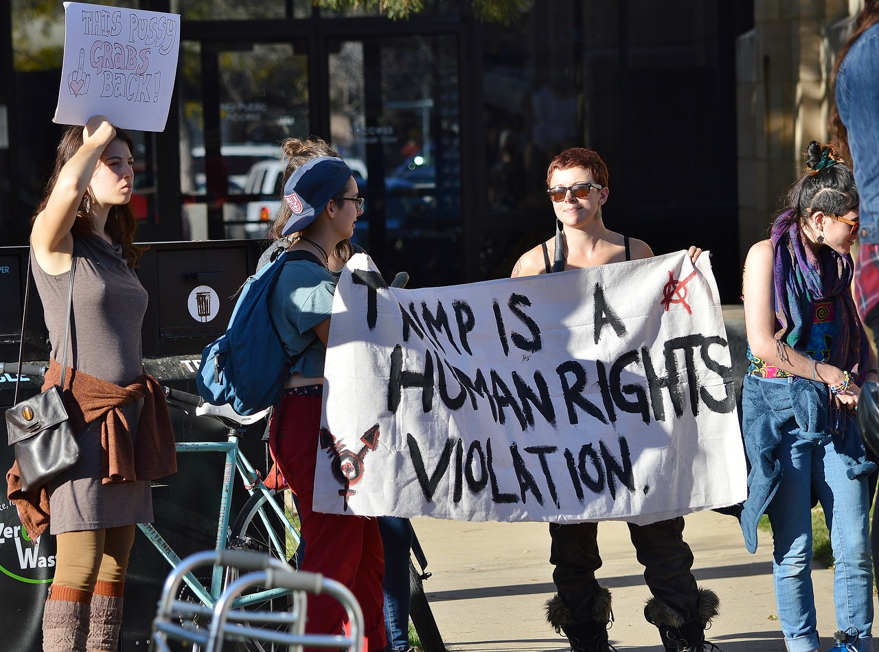 """Two women hold a banner """"Trump Is A Human Rights Violation"""" at a rally."""