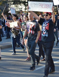 "Young man wearing Obama shirt  carries sign above head ""#NotMy President"", while marching in protest aginst President-Elect Donald Trump."