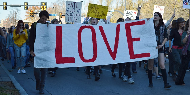 """Two protesters carry large banner that says """"Love"""" while marching in opposition to Donald Trump."""