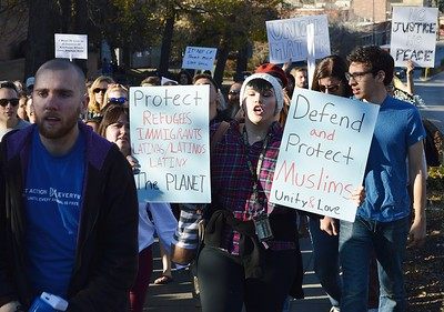 Young woman carries two sign while marching in protest against Donald Trump.