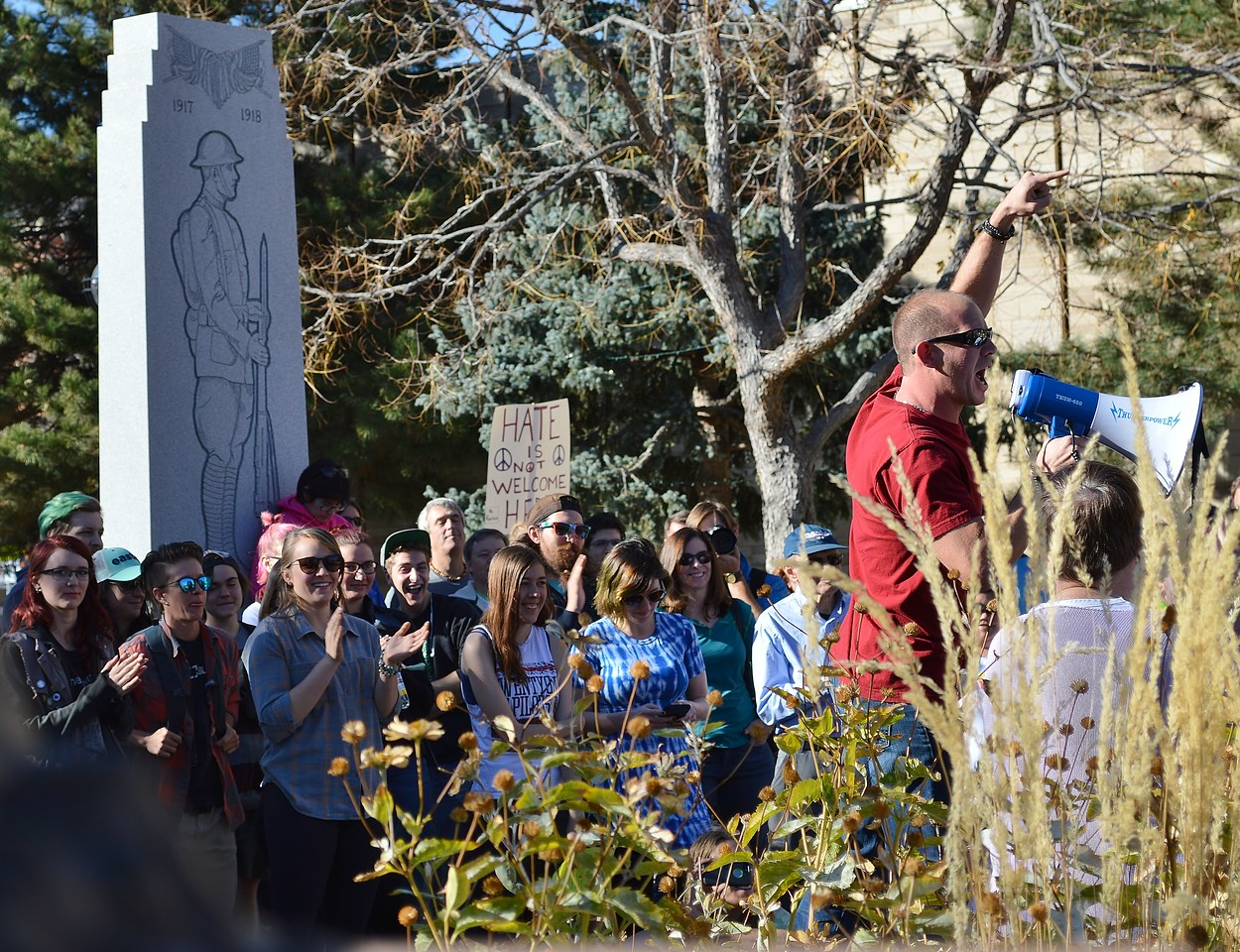 Speaker at anti Donald Trump rally raises hand in the air while speaking throough a bullhorn.