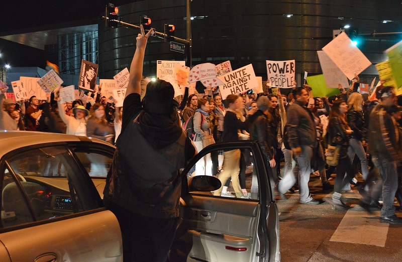 Woman gets out of car and  raises hand in the air in the peace sign and line of anti Donald Trump protesters  march by.
