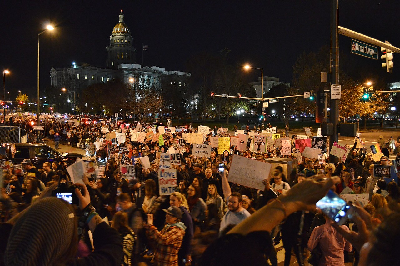 Long line of protesters at anti Donald Trump march, Colorado State Capitol dome in the background.