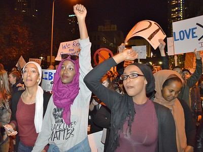 Young woman holding fist in the air at protest march against Donald Trump.