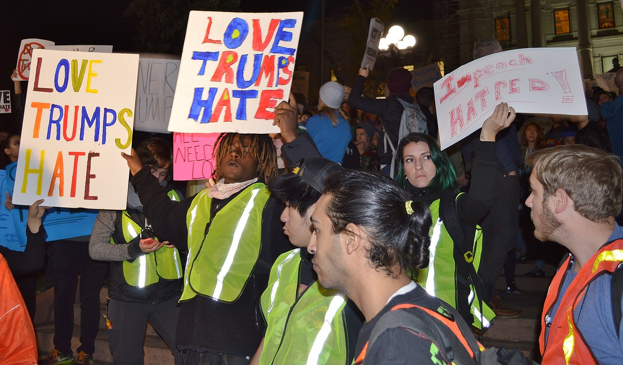 African American man holds up Love Trumps Hate sign at anti Trump protest.