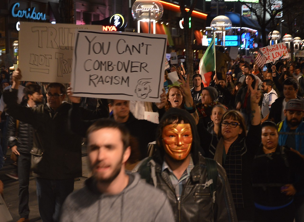 """Long line of marchers at anti Donald Trump protest, including one wearing """"anonymous/Guy Fawkes"""" mask."""