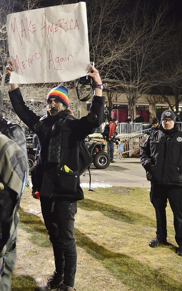 Protester holds up sign about US & Mexico at speech by Milo Yiannopoulos at the Univ of Colorado in Boulder.