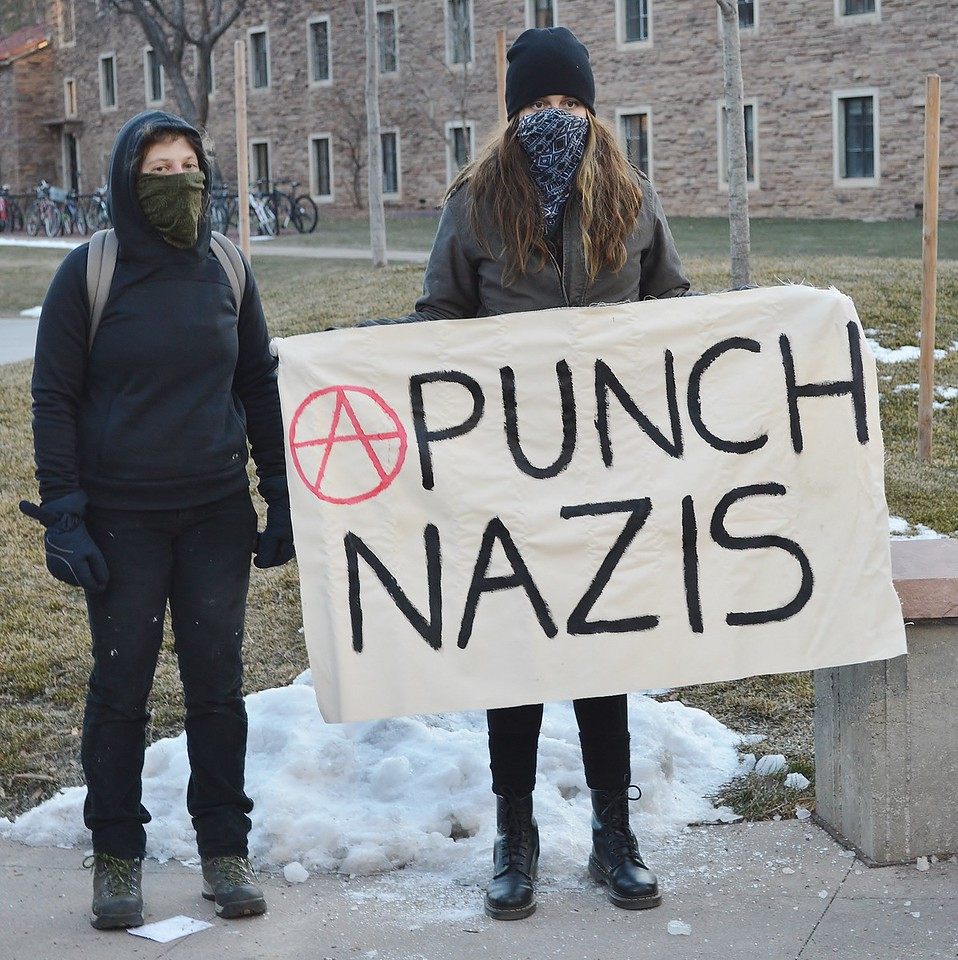 "Young woman holding ""Punch Nazis"" sign at protest against Milo Yiannopoulos speech at Univ of Colorado in Boulder."