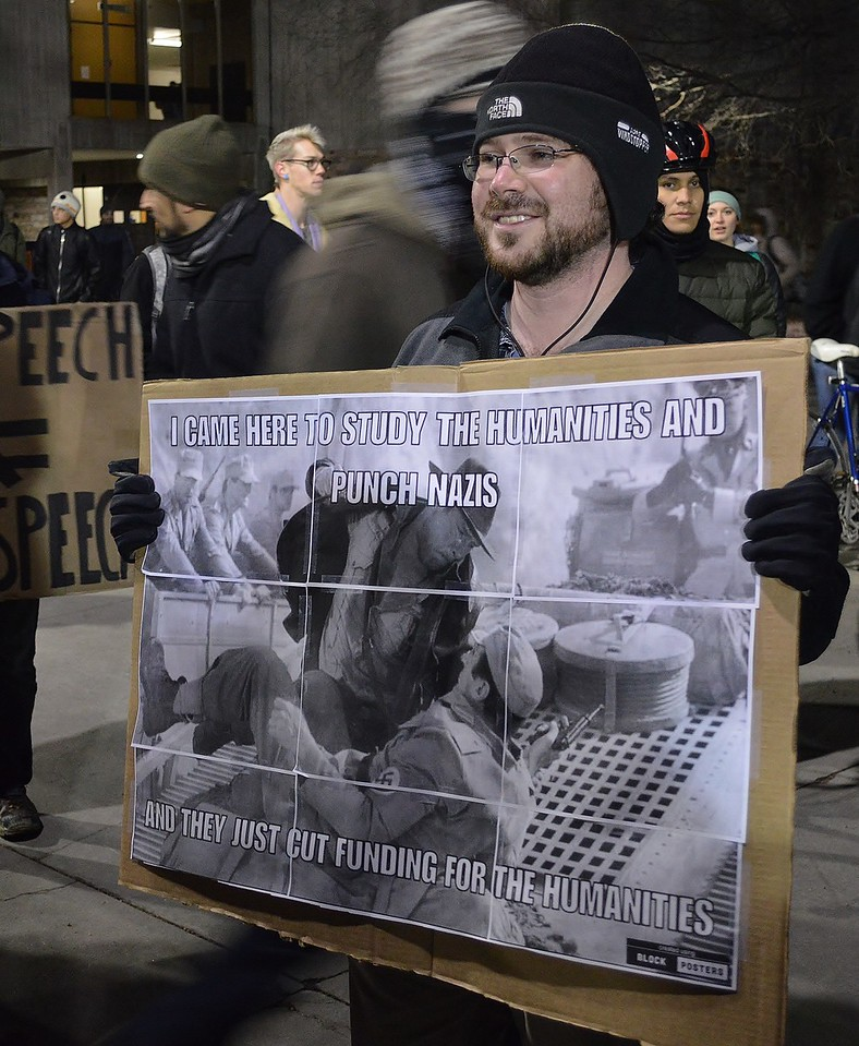 "Man at protest against speech at Univ of Colorado in Boulder by Milo Yiannopoulos, holds picture of ""Indiana Jones"" punching a Nazi."