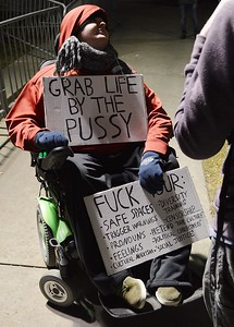 Man in wheelchair holds anti-liberal signs at protest against Milo Yiannopoulos speech in Boulder at the Univ of Colorado.