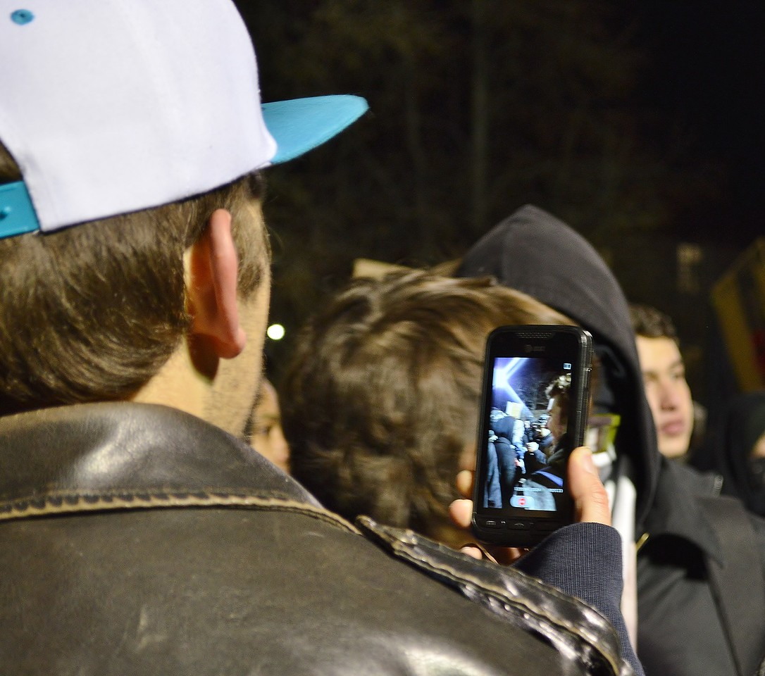 Protester takes pictures with cellphone at speech by Milo Yiannopoulos at Univ of Colorado in Boulder.