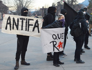 "Anarchist protesters in black, holding 'ANTIFA"" banner at Milo Yiannopoulos speech at Univ of Colorado in Boulder."