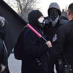 Anarchist protesters in black talking to a police officer at Milo Yiannopoulos speech at Univ of Colorado in Boulder.