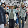 "This woman displays a sign with a quote from Benito Mussolini during the march to ""Defend Our Constuitution."