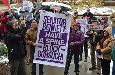 Opponents of Neil Gorsuch, President Trump's nominee to the Supreme Court, rallied in front of Senator Michael Bennett's office before presenting a Bennett staff member with petitions and a model of a spine.