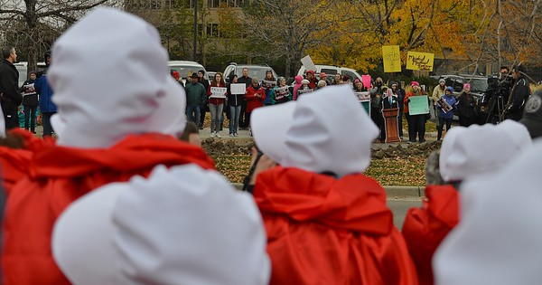 """Protesters, some in """"Handmaid's Tale"""" costumes, line the street outside a Republican party fundraiser in Denver, where Vice President Mike Pence was speaking."""