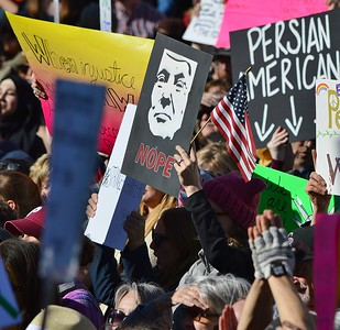 Protesters raises American flag and anti-Trump sign at rally against immigration and refugee ban.
