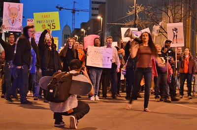 """Young woman with bullhorn led """"Not My President's Day"""" marchers through downtown Denver."""