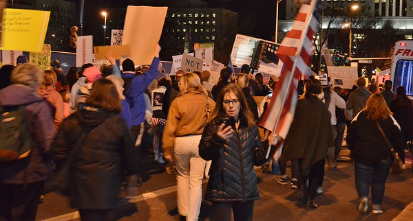 """This woman, carrying an American flag, stops to check her cellphone during the """"Not My President's Day"""" march in Denver."""