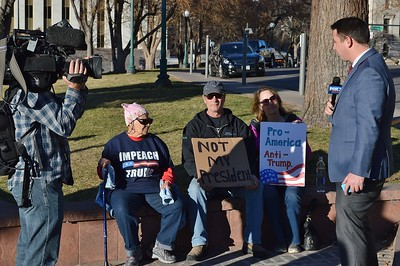 Protesters opposed to President Trump being interviewed by local TV news reporter.