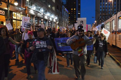 """This man playing guitar and harmonica was among the hundreds who joined the """"Not My President's Day"""" march throught downtown Denver."""