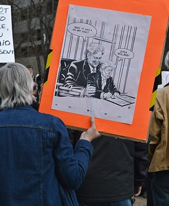 Protester at rally holding sign with cartoon about President Trump and advisor Steve Bannon.