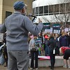 Speaker at Resist Trump Tuesdays rally gesturing to crowd of protesters.
