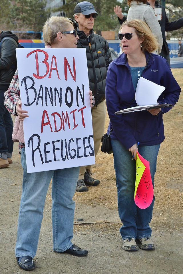 """Woman holding pro refugee, anti Steve Bannon sign at """"Resist Trump Tuesdays"""" rally in Denver."""