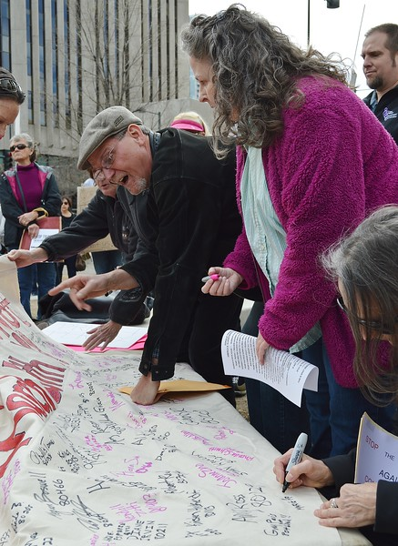 """Large banner being signed by protesters at """"Resist Trump Tuesday"""" in Denver, Co."""