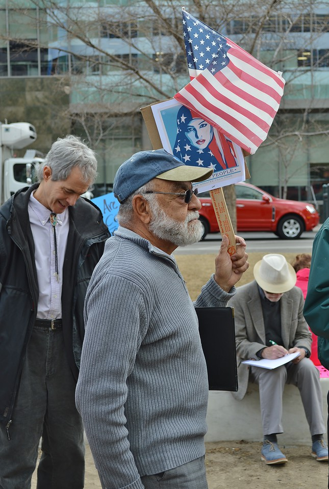 Anti Trump protester holding American flag.